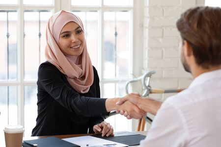 Pleasant smiling arabian female hr manager in hijab shaking hands with male job applicant. Young happy arabic businesswoman welcoming partner or making agreement with client at meeting in office.