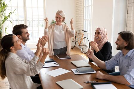 Overjoyed middle aged female team leader celebrating corporate success with young multiracial colleagues at business meeting in office. Happy mixed race teammates succeed in profitable project.