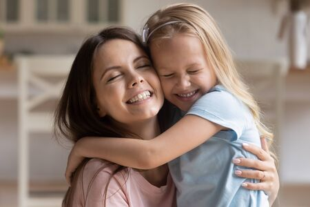Close up view faces of beautiful preschool daughter embracing showing love to mother, relative people cuddling with closed eyes enjoy tender moment expressing deep devotion bonding and care concept