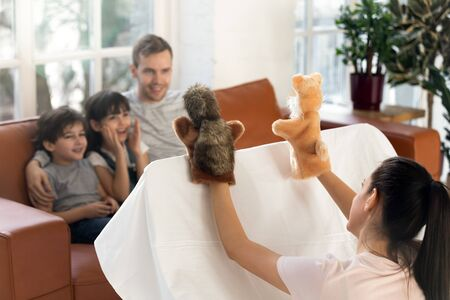 Happy father with cute siblings watching mom puppet show. Smiling young family sitting together on sofa at home, mother play muppet toys do theatre performance for small children.