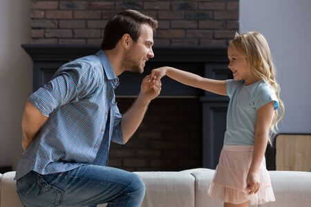 Side view dad standing one bended knee making curtsey in front of kid girl took her hand for kiss, concept of gentlemen gesture, deep devotion and connection and endearment between father and daughter