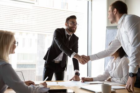 Smiling multiracial businessmen shake hands get acquainted greeting at team meeting in office, motivated diverse male business partners handshake closing deal after successful negotiation at briefing