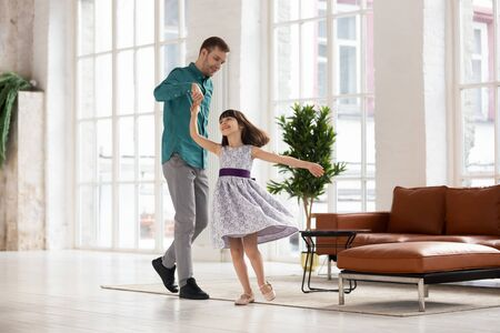 Happy loving father leading in dance holding daughter hand up. Smiling dad and adorable daughter dancing to favorite song at home. Having fun together in living room, family weekend concept.