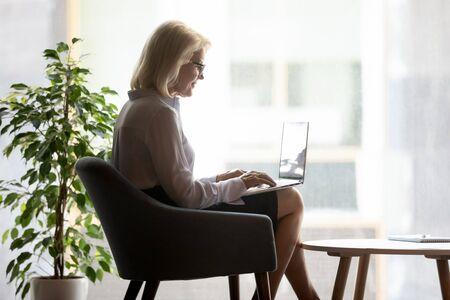 La empresaria caucásica de mediana edad se sienta en una silla en la oficina moderna trabajando en la computadora portátil enviando mensajes de texto o enviando mensajes con los clientes, empleada madura que usa la computadora, revisa el correo, navega por internet inalámbrico