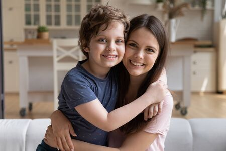 Son and mom sitting on couch at home and embracing celebrating mothers day looking at camera. New mum for adopted small kid boy, relative people elder sister and younger brother warm relations concept Stock Photo