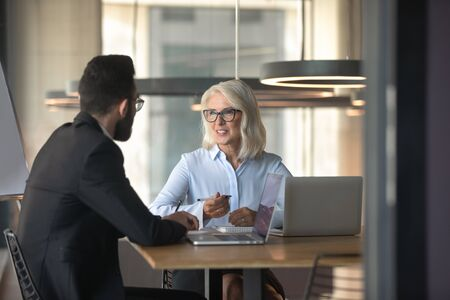 Multiethnic diverse businesspeople sit at office desk brainstorm discussing business ideas or plans together, multiracial colleagues talk consider share thoughts on briefing, cooperation concept