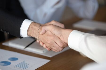 Close up of businessmen shake hands at meeting get acquainted or greeting in office, male colleagues or business partners handshake closing deal making agreement at negotiation, partnership concept