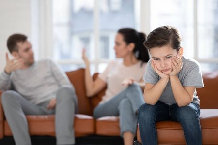 Close up little boy suffering from parents conflict sitting at couch. Sad son frustrating hear mother and father fighting arguing and bad situation, family conflict, divorce. Stock Photo