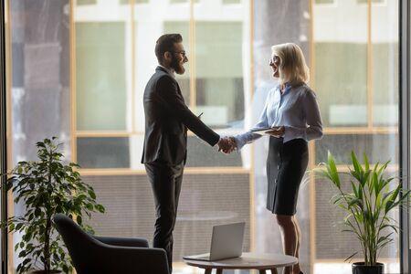 Gli uomini d'affari multirazziali sorridenti stanno in ufficio moderno stringono la mano chiudendo l'accordo dopo negoziati di successo, felici diversi colleghi o partner stringono la mano stringono un accordo, concetto di partnership