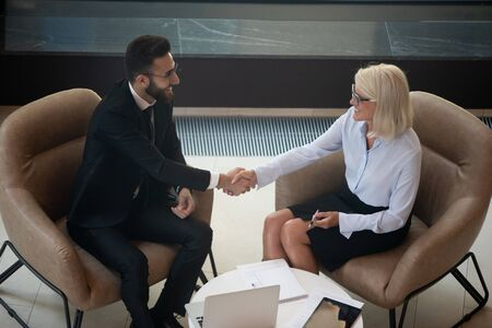 Top view of smiling multiracial businesspeople shake hands greeting or get acquainted at business meeting in office, happy diverse partners or colleagues handshake closing deal or making agreement Banco de Imagens