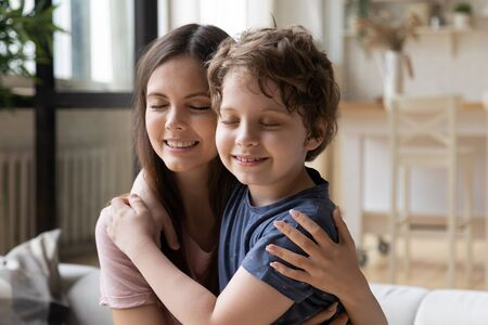 Caring loving young mother or older sister cuddle little son or younger brother, relative people closed eyes enjoy tender moment showing deep devotion care and love, next generation offspring concept