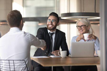 Los empresarios multirraciales sonrientes se dan la mano del candidato de trabajo masculino para familiarizarse en la reunión o el saludo, el apretón de manos de diversos empleadores felices cierra un trato comercial después de una negociación exitosa en la oficina