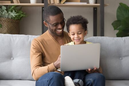 Smiling black young dad sit on couch holding cute little son watching video on laptop together, happy african American father have fun playing computer game with preschooler child relaxing at home