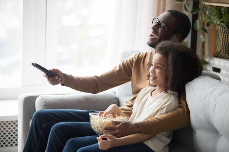 Smiling african American young dad relax on couch with cute preschooler daughter watching TV together, happy black father sit rest on sofa with girl child use remote enjoy movie time with popcorn