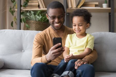 Smiling african American young dad sit on couch with cute biracial son watching funny video on smartphone, happy black father and preschooler boy child relax at home play game on cellphone together 스톡 콘텐츠