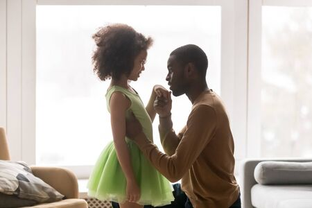 Young african American dad kneel kiss hand of beautiful biracial daughter wearing green dress, caring black father enjoy tender close moment with girl child dancer show affection and love at home