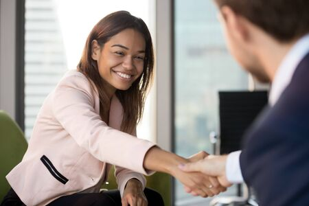 Smiling African American businesswoman shaking hand of businessman, business partners, candidate and hr manager handshaking, greeting each other, making deal, partnership agreement at meeting