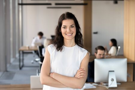 Head shot portrait of successful smiling businesswoman with arms crossed standing in office, looking at camera, happy female employee, team leader posing for company photo, beautiful woman at work Banco de Imagens