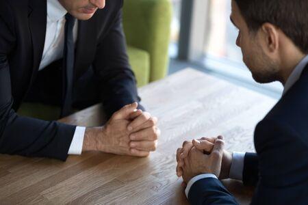 Cerrar dos negociadores de hombres de negocios con las manos juntas, debatir el concepto de diálogo, oponentes sentados frente a la mesa, negociaciones de socios comerciales, confrontación, lucha por el liderazgo, conflicto
