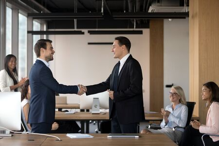 Executive manager shaking hand of successful employee at company meeting, congratulating with promotion for good work results, diverse colleagues applauding and supporting, greeting new worker