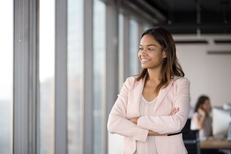 Smiling successful African American businesswoman with arms crossed standing in office, looking in window, thinking about new project or business strategy, dreaming, business vision concept