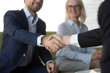 Smiling businessman shaking hand of business partner at meeting, greeting, acquaintance, friendly hr manager handshaking with candidate on job interview, making deal or agreement close up Banco de Imagens
