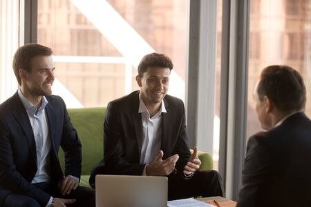 Smiling Arabian businessman talking with business partner at meeting in modern office, executive manager consulting client, business people discussing project results, strategy, planning