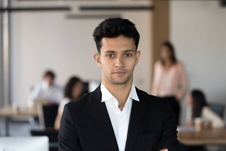Head shot portrait of confident middle eastern businessman standing in office with colleagues on background, looking at camera, successful team leader, employee in suit posing for photo at workplace