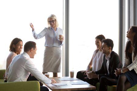 Sorridente donna d'affari matura che tiene briefing con diversi dipendenti, capo squadra che si congratula con il subordinato con successo aziendale, colleghi felici attività di team building, formazione del personale aziendale