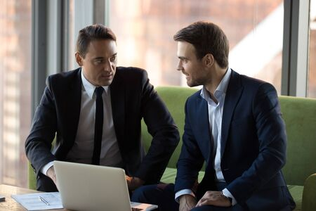 Successful businessmen in suits discussing online project, business strategy in office, employees working together, business partners negotiations, friendly executive manager consulting client