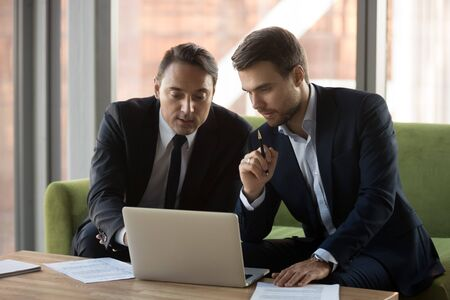 Serious businessmen working together, using laptop, looking at screen, discussing project, startup at meeting in office, business partner negotiations, mentor helping intern with corporate software