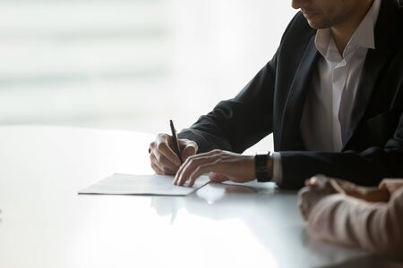 Close up confident businessman signing contract, partnership agreement, client, customer putting signature on legal document, making successful business deal, investment, taking loan or insurance