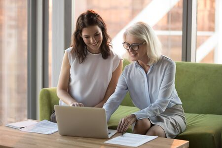 Smiling mature businesswoman with colleague using laptop together, working on online project, mentor helping young employee intern with corporate software, executive manager consulting client