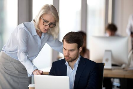 Mature businesswoman mentor explaining intern corporate software, focused businessman looking at laptop screen, working on online project in office, supervisor check employee work results