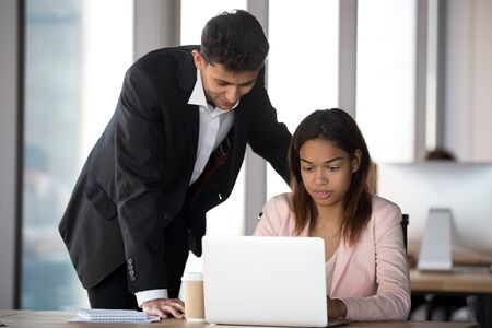 Friendly Arabian mentor helping African American intern with corporate software, businesswoman using laptop, working on online project, supervisor check employee work results, assistance concept
