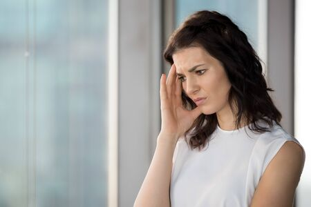 Upset businesswoman suffering from headache in office, stressed exhausted woman thinking about trouble at work, tired sad employee feeling unwell, touching temples, health problem concept close up