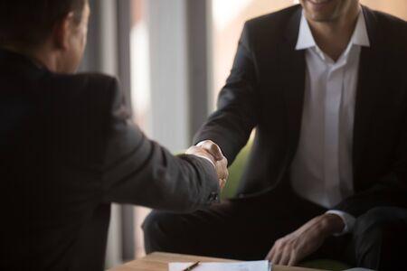 Close-up zakenlieden handenschudden na succesvolle onderhandeling, deal sluiten, contract ondertekenen, zakelijke partners begroeten, respect en eenheid tonen, kennis, eerste indruk tijdens vergadering Stockfoto