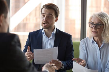 Angry businessman and mature businesswoman arguing with business partner at meeting in office, dissatisfied by contract terms, unsuccessful negotiation, employees disputing about paperwork failure Banco de Imagens
