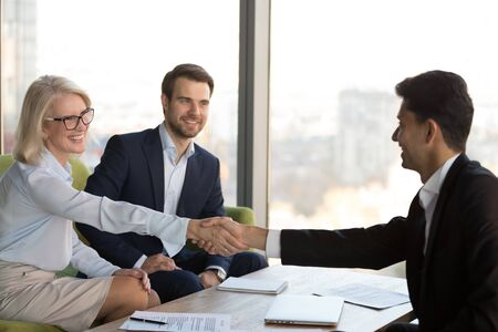 Smiling mature businesswoman shaking hand of business partner after signing contract at meeting, celebrating partnership agreement, making investment deal, handshaking as respect or gratitude