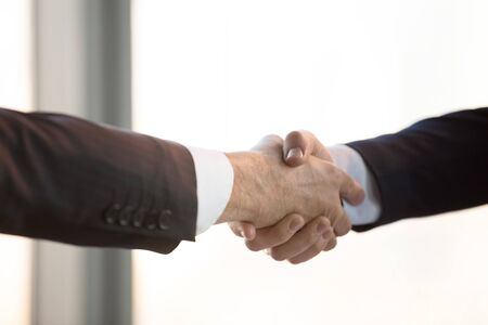 Close up two businessmen in suits handshaking after successful negotiation, business partners greeting, making deal, showing respect and unity, acquaintance, first impression at meeting
