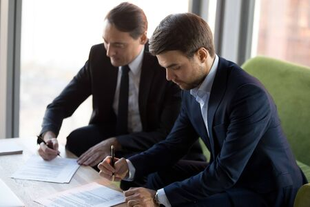 Successful businessmen in suits signing contract, business partners making partnership agreement, commercial deal, client putting signature on legal document, writing on paper, taking loan Banco de Imagens