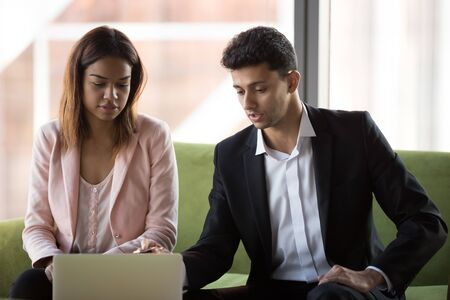 Arabian mentor helping African American intern with corporate software, executive manager explaining to employee online project, pointing on laptop screen, finance advisor making offer to client