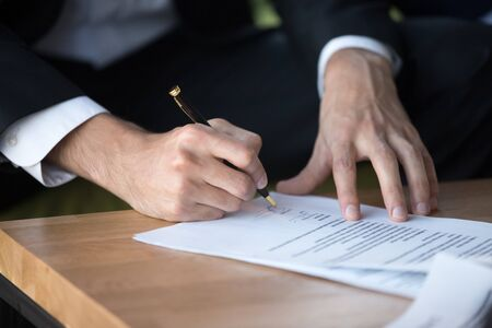 Close up businessman signing contract, partnership agreement after successful negotiation, making legal deal, putting signature, hiring process, candidate filling job agreement, good deal Stockfoto
