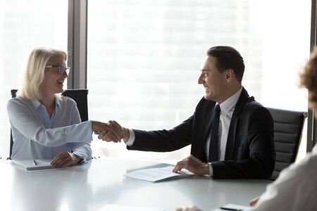 Excited mature businesswoman shaking hand of business partner, smiling businessman at meeting, making partnership agreement, commercial deal, successful negotiate, celebrating contract signing Banco de Imagens
