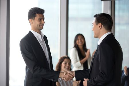 Team leader shaking hand of smiling Arabian businessman at meeting, executive manager congratulating employee with promotion for good work, greeting new worker, diverse colleagues applauding close up Banco de Imagens
