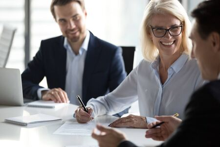 Smiling happy mature businesswoman signing contract, partnership agreement at meeting after successful negotiation, business partners making commercial deal, putting signature on legal document