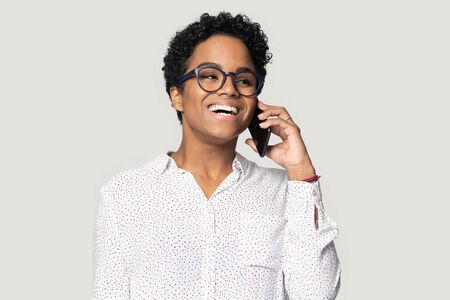 Head shot excited happy smiling african american young woman in eyeglasses talking on cellphone with friend, listening to good news, business success or win notice, isolated on grey studio background. Stockfoto