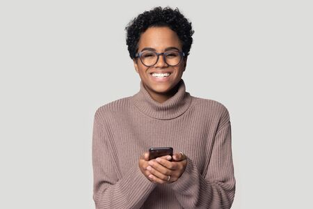 Head shot excited happy african american young woman in warm sweater standing with smartphone in hands, laughing, feeling joyful, received good news, win notice, isolated on grey studio background. Stockfoto