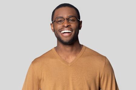 Head shot close up portrait happy smiling african american man in casual sweater looking at camera. Cheerful millennial black guy in round glasses posing for photo, isolated on grey studio background.