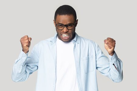 Irritated angry mad millennial african american guy wearing eyeglasses clenching both hands in fists, demonstrating aggressive mood, isolated on grey studio background, negative emotion concept.
